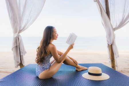 Portrait beautiful young asian woman reading book with happy smile relax in lounge bed chair on the beach sea ocean for leisure travel in vacation