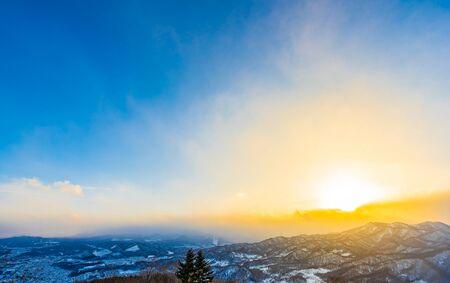 Beautiful landscape with mountain around tree in snow winter season at sunset time in Sapporo Hokkaido Japan Stock Photo