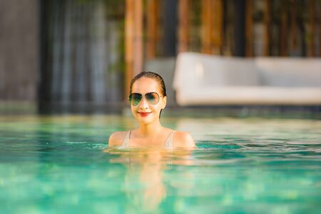 Portrait young beautiful asian woman happy smile and relax in swimming pool around hotel resort for leisure travel in holiday vacation Stock fotó