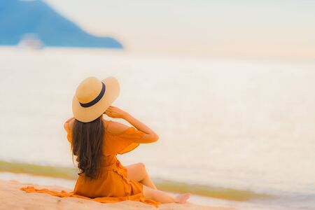 Portrait beautiful young asian woman happy smile relax on the beach sea ocean at sunset time in holiday vacation