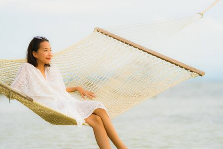 Portrait beautiful young asian woman sitting on hammock around sea beach ocean for relax in holiday vacation travel concept Stock fotó