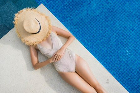 Portrait young asian woman relax smile happy around swimming pool in hotel and resort for holiday vacation travel concept Zdjęcie Seryjne - 129836969