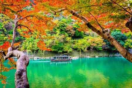 Beautiful Arashiyama river with maple leaf tree and boat around lake in Autumn season Kyoto Japan