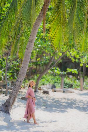 Portrait young asian woman smile happy around beach sea ocean with coconut palm tree for travel in holiday vacation