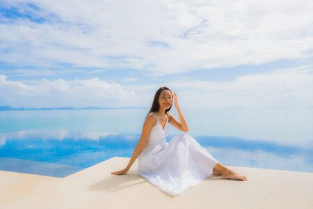 Portrait young asian woman relax smile happy around swimming pool in hotel and resort for holiday vacation travel concept Zdjęcie Seryjne - 130028395