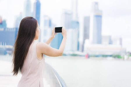 Beautiful asian woman using smartphone or mobile phone for taking a photos