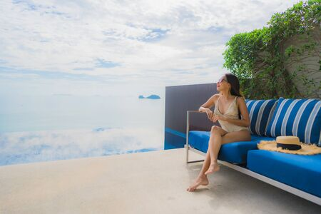 Portrait young asian woman relax smile happy around swimming pool in hotel and resort for holiday vacation travel concept Zdjęcie Seryjne - 130042384