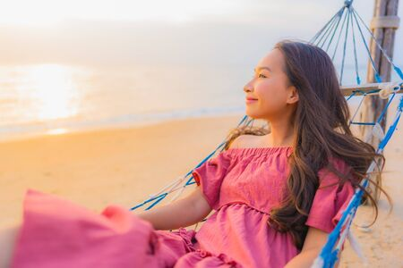 Portrait beautiful young asian woman sitting on the hammock with smile happy neary beach sea and ocean for leisure travel and vacation at sunset time
