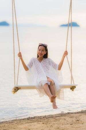 Portrait beautiful young asian woman sitting on the swing around beach sea ocean for relax in holiday vacation concept