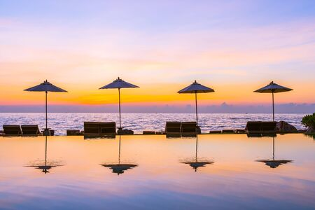 Umbrella and chair around swimming pool for leisure travel and vacation nearby sea ocean beach at sunset or sunrise time Stock fotó