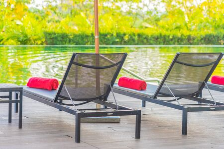 Umbrella and chair around swimming pool in hotel resort for leisure vacation and travel