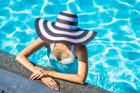 Beautiful young asian woman with hat in swimming pool for travel and vacation concept Stock fotó