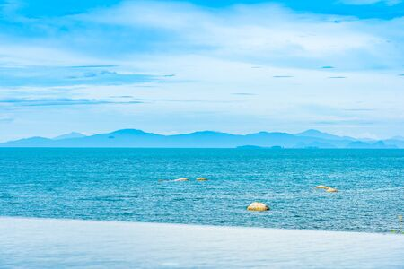 Beautiful outdoor infinity swimming pool in hotel resort with sea ocean view and white cloud blue sky for holiday vacation and travel