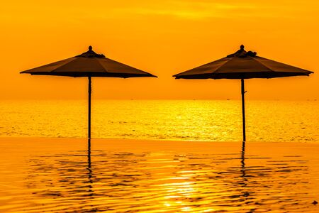 Umbrella and chair around swimming pool neary sea ocean beach at sunrise or sunset time for leisure travel and vacation Stock fotó