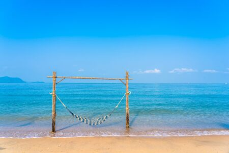 Empty hammock swing on the beautiful beach and sea for holiday vacation travel and leisure concept