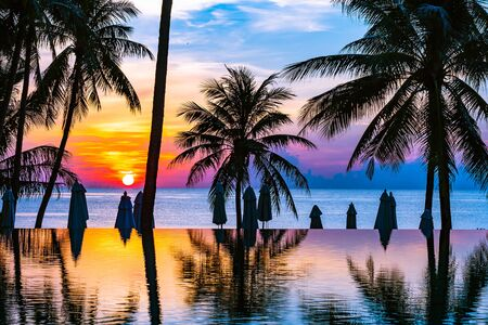 Beautiful outdoor tropical nature landscape of swimming pool  with coconut palm tree umbrella and chair nearly sea ocean beach at sunrise time