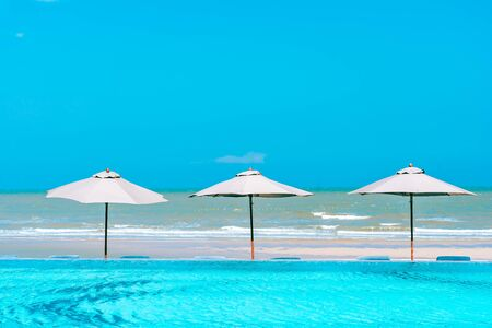 Umbrella and chair around swimming pool neary beautiful landscape of sea ocean beach with blue sky and white cloud for leisure travel and vacation Stock fotó