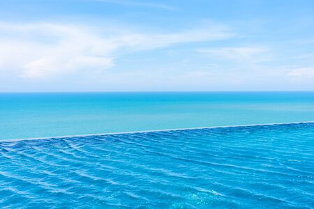 Beautiful outdoor landscape of infinity swimming pool in hotel resort with sea ocean on white cloud blue sky view for leisure travel in holiday vacation Stock fotó