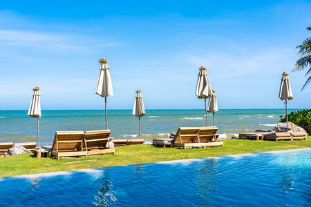 Beautiful outdoor nature landscape with bed deck chair around swimming pool in hotel resort on blue sky background for travel and vacation concept Фото со стока