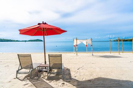 Beautiful outdoor tropical beach sea ocean with umbrella chair and lounge deck around there on white cloud blue sky background for holiday vacation travel Stock Photo