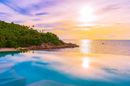 Beautiful outdoor infinity swimming pool with coconut palm tree around beach sea ocean at sunrise or sunset time for holiday vacation travel background Фото со стока