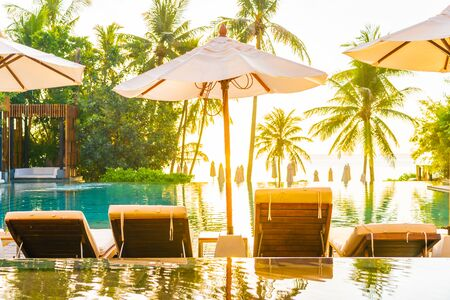Beautiful outdoor tropical nature landscape of swimming pool in hotel resort with coconut palm tree umbrella and chair nearly sea ocean beach at sunrise time Stock Photo