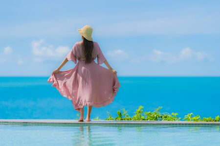 Portrait young asian woman relax smile happy around outdoor swimming pool in hotel resort with sea ocean view in holiday vacation concept Фото со стока