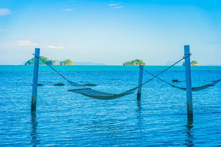 Empty hammock around beautiful beach sea ocean for relax in holiday vacation travel concept Imagens