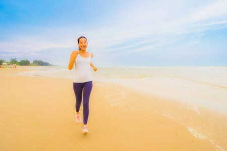 Portrait beautiful young sport asian woman exercise by run and jogging on the outdoor nature beach and sea for healthy