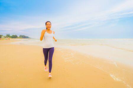 Retrato hermoso joven deporte mujer asiática ejercicio por correr y trotar en la naturaleza al aire libre en la playa y el mar para una salud saludable Foto de archivo