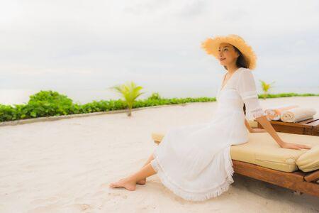 Portret mooie aziatische vrouw draagt hoed met glimlach, gelukkige vrije tijd op het strand en de zee-oceaan in vakantievakantie