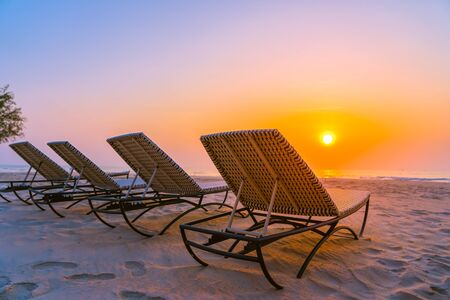 Empty chair on the tropical nature beach and ocean sea at sunrise or sunset time for leisure travel and vacation