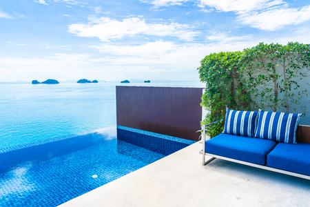 Hermosa piscina al aire libre de lujo con vista al mar en el cielo azul nube blanca alrededor de la almohada en la decoración del sofá para vacaciones y viajes