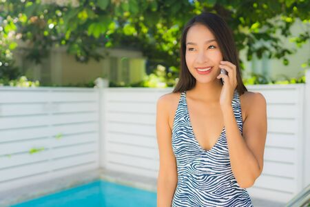 Portrait beautiful young asian woman happy smile talk mobile phone around swimming pool in leisure vacation time Stock fotó