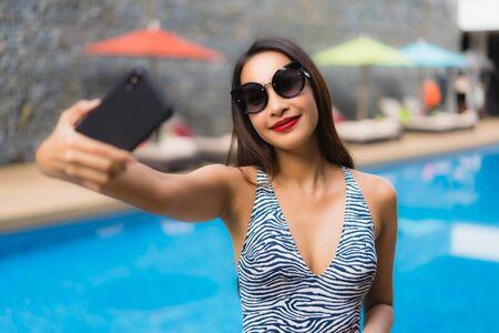 Retrato hermosa mujer asiática con teléfono móvil alrededor de la piscina al aire libre en vacaciones de vacaciones