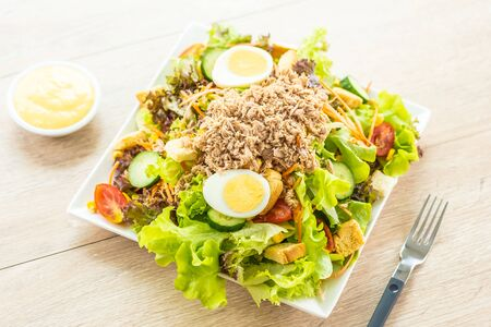 Tuna meat and eggs with fresh vegetable salad and sauce - Healthy food concept