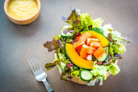 Crab sticks meat with fresh vegetable salad in wood bowl with mayonnaise sauce - Healthy food style