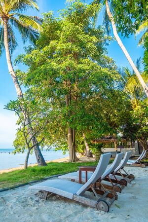 Beautiful outdoor view with umbrella and chair on the beach and sea with coconut palm tree for vacation and travel Фото со стока
