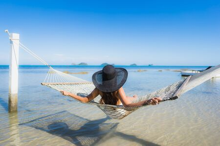 Portrait beautiful young asian woman sitting on hammock around sea beach ocean for relax in holiday vacation travel concept Фото со стока