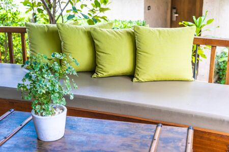 Vase plant on table decoration with pillow on sofa chair outdoor view