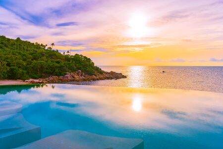 Beautiful outdoor infinity swimming pool with coconut palm tree around beach sea ocean at sunrise or sunset time for holiday vacation travel