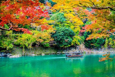 Beautiful Arashiyama river with maple leaf tree and boat around lake in Autumn season Kyoto Japan Фото со стока - 131349395