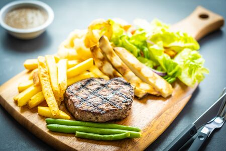 Grilled beef meat steak with french fries sauce and fresh vegetable on wooden cutting board Фото со стока - 131349476