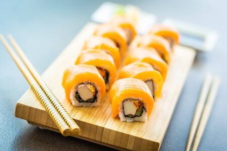 Salmon fish meat sushi roll maki on wood plate with wasabi and soy sauce - Japanese food style Фото со стока