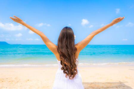 Portrait schöne junge asiatische Frau glückliches Lächeln Freizeit am Strand Meer und Ozean mit blauem Himmel weiße Wolke für Urlaubsreisen Standard-Bild