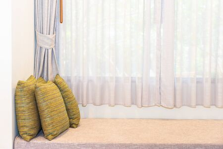 Beautiful comfortable pillow on sofa decoration with curtain interior of room Фото со стока
