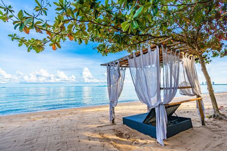 Empty bed chair and lounge on the tropical beach sea ocean with white cloud on blue sky for leisure travel and in holiday vacation Фото со стока