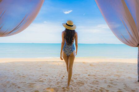 Portrait beautiful young asian woman happy smile relax on the tropical beach sea ocean for leisure travel in holiday vacation