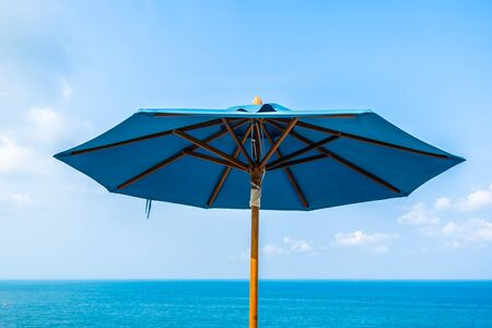 Blue color of umbrella with cloud sky and sea ocean for leisure travel and vacation Фото со стока - 131350694