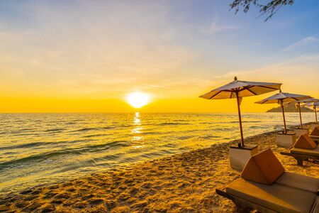 Umbrella and chair with pillow around beautiful landscape of beach and sea at sunrise or sunset time for holiday vacation and travel Фото со стока - 131351122